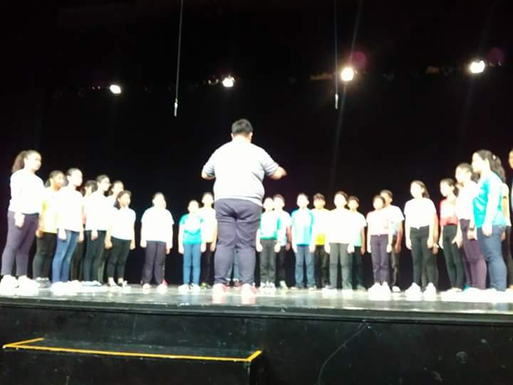 Mr. Kennedy Tabon (back to the camera) conducts CADENCE at the Aliw Theatre stage for a berth at the MBC Chorale Competition.