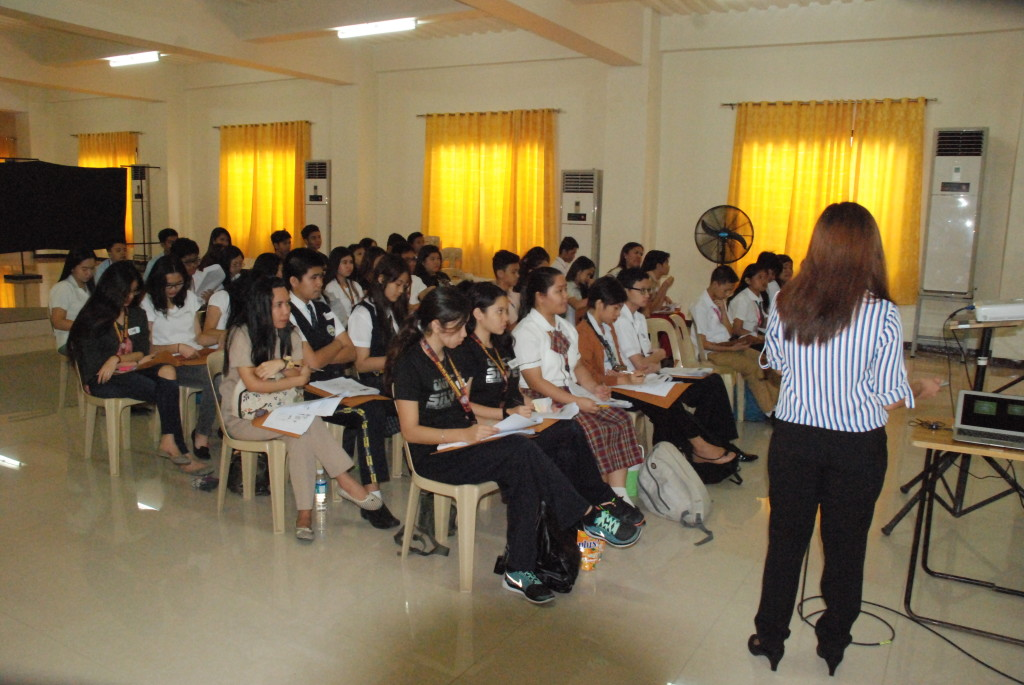 The participants from different schools listen intently to a doctor during the seminar.