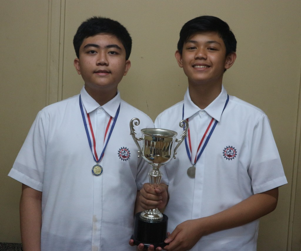 Marc Luis Menquito and Daniel Aiken Eduardo hold their trophy and wear their medals as Champions in the MTAP Math Challenge.